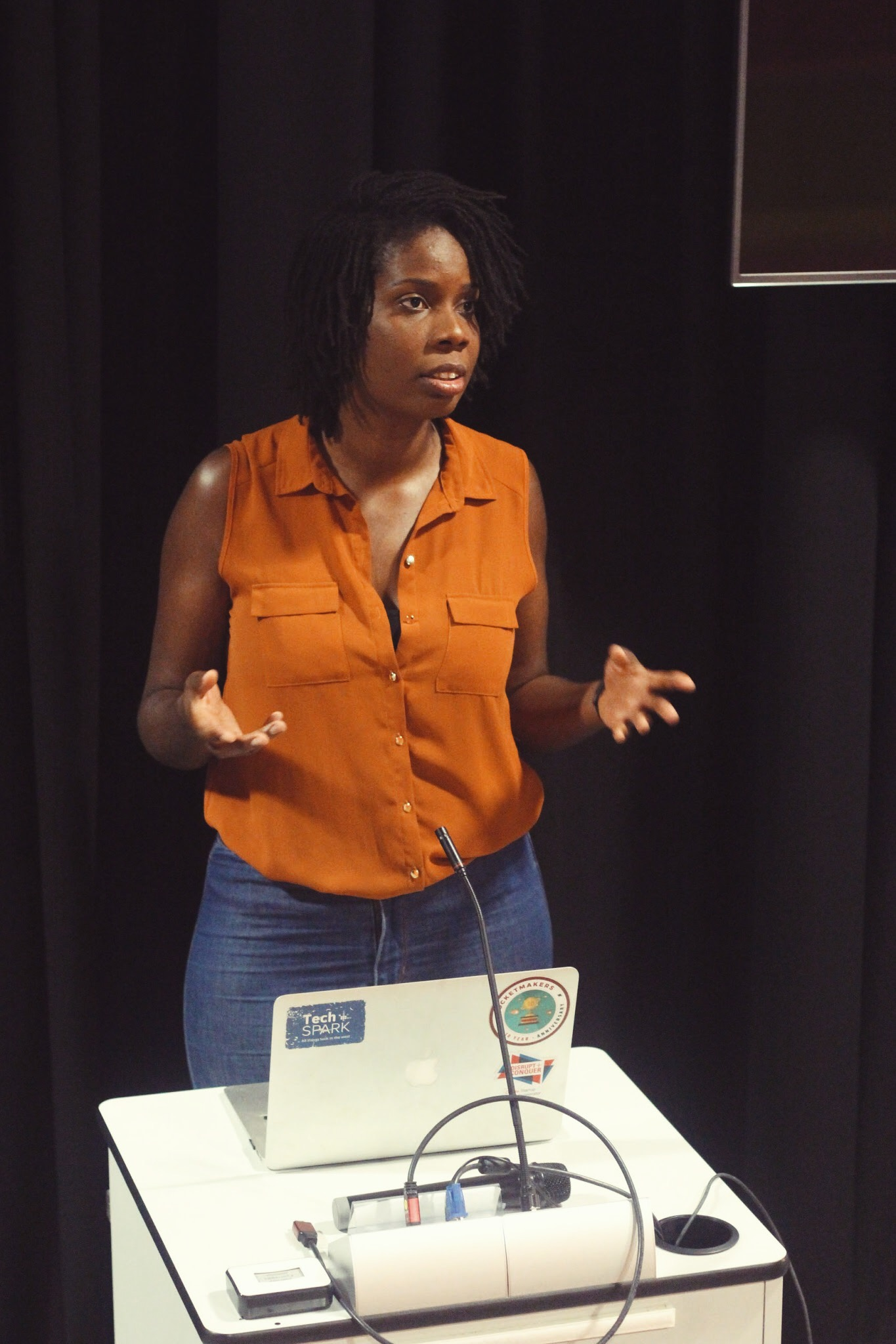 A black woman named Joyann Boyce standing at a podium giving a talk. She is behind a black back drop, she has a laptop in front of her and a microphone. She's wearing an orange top and blue jeans.
